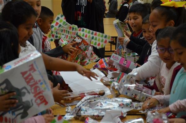 Children unwrapping gifts