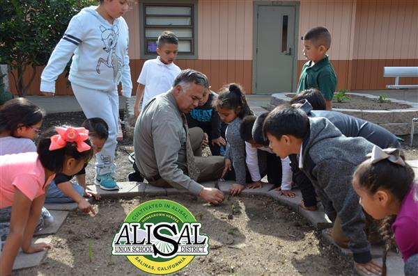Miguel Porras working with students in the garden
